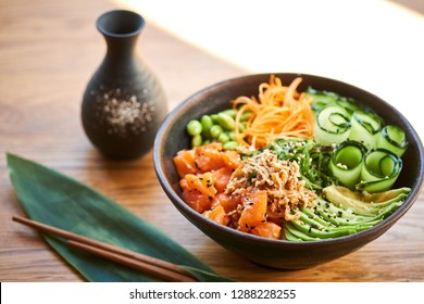 Poke bowl, chopsticks and Japanese alcoholic drink sake on table. Traditional Hawaiian and Japanese cuisine. Healthy food.