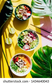 Poke bowl are the latest in food industry, a bowl with vegetables and salmon on a yellow pink background with giant monstera leaf around.