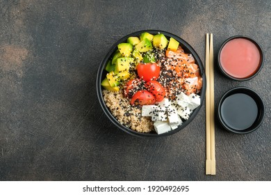 Poke bowl with quinoa, salmon, avocado, feta cheese and kimchi sauce on a dark background top view with copy space. Home delivery food.