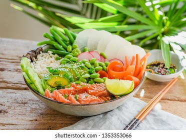 Poke bowl with salmon, avocado, edamame beans, vegetables and rice on wooden background and palm leaves. Sushi bowl.Trendy healthy food.