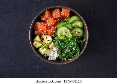 poke bowl with salmon over dark background. top view