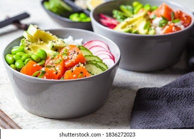 Poke bowl with salmon, rice, avocado, edamame beans, cucumber and radish in a gray bowl. Hawaiian ahi poke bowl, gray background.