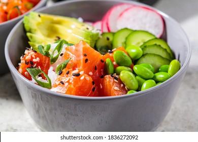 Poke bowl with salmon, rice, avocado, edamame beans, cucumber and radish in a gray bowl. Hawaiian ahi poke bowl, gray background. - Shutterstock ID 1836272092