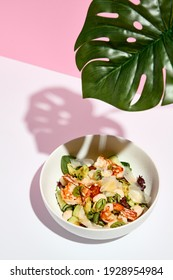 Poke bowl with shrimp and vegetables. Restaurant seafood appetizer on white table with pink wall. Day sunlight with hard shadow of monstera palm leaves. Summer or spring restaurant food concept