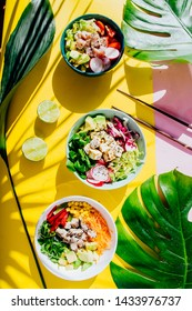 Poke bowl are te last trend in food industry, a bowl with vegetables and salmon on a yellow pink background with giant monstera leaf around.