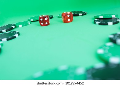 Poker black and green chips with dices on green background. Close up. Copy space