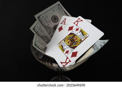 Poker Cards King Ace of diamond high card with 300 Dollar bills on black background Cocktail glass