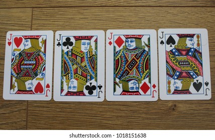poker cards on a wooden backround, set of jacks of clubs, diamonds, spades, and hearts