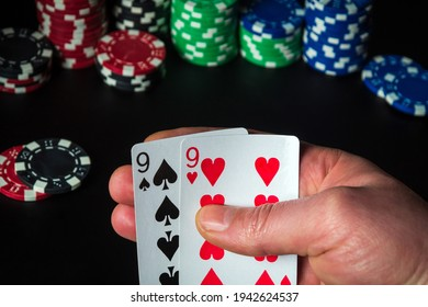 Poker cards with one pair combination. Close up of a gambler hand is holding playing cards in casino