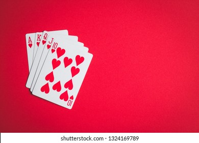 Poker cards. Royal flush on red table.