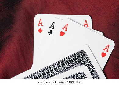 poker cards. three aces on red fabric