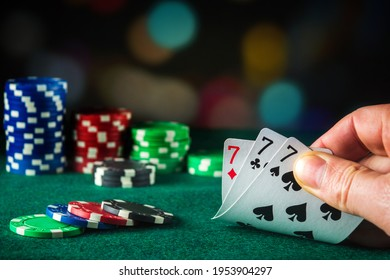 Poker cards with three of a kind or set combination. Close up of gambler hand takes playing cards in poker club