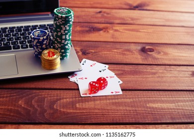 Poker chips and bitcoins on keyboard, play cards and dice. Poker online, payment by bitcoin concept.