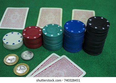 Poker chips, cards and some coins of  brazilian money (one real and fifty centavos) above green cloth.
