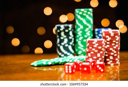 Poker Chips in casino gamble wooden table on light bokeh background.Dice, lottery, gambling,Poker chips and casino games concept.