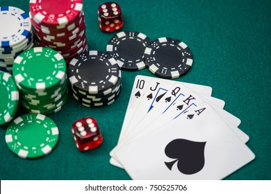 Poker chips, dice and Royal Flush card combination on gambling table
