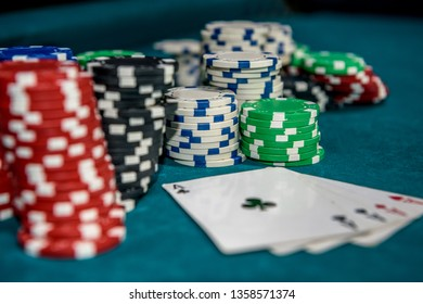 Poker chips with four aces at table in casino