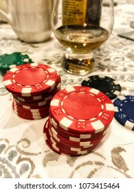 Poker chips with glass of wine on the table, closeup