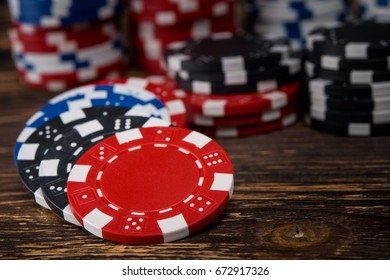 Poker chips on a wooden table, scattered with a background
