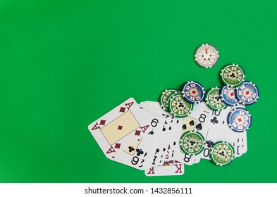 poker chips stack and playing cards on green table. empty space for text and design. top view