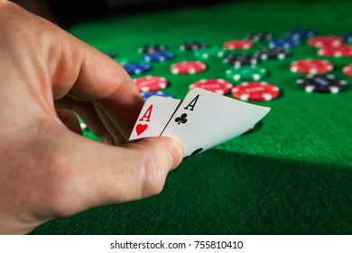 Poker chips with two aces on green background.