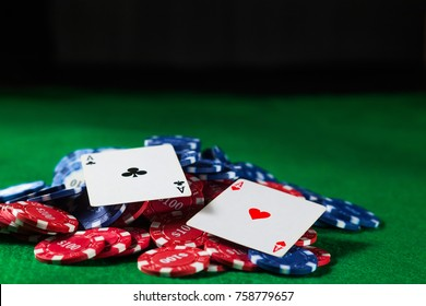 Poker chips with two cards aces on a green table on a black background