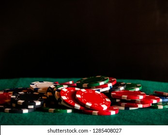 Poker chips of various colors on a green mat