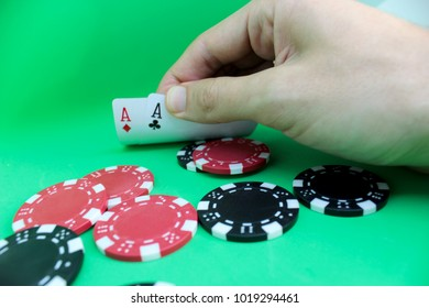 Poker concept. Man's hand holds poker cards and chips. Green background
