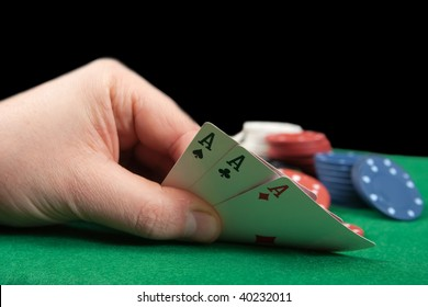 Poker gambler  in casino. Close-up of hand with three aces.