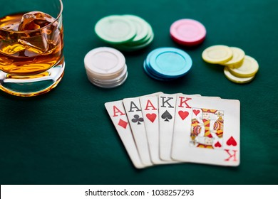 Poker hand of full house, chips and a glass of whiskey on green broadcloth