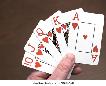 Poker hand, royal flush in hearts, brown background
