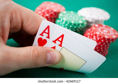 Poker hand with two aces. Some casino chips in the background over a green gaming table.
