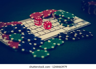 Poker online addiction. Some poker chips and a couple of red dices on a keyboard. Betting on Internet concept.
