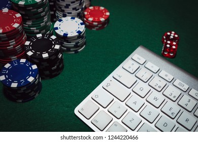 Poker online website concept. Side view of a green poker table with some poker chips, red dices and a white keyboard. Gambling online idea. Win money on Internet