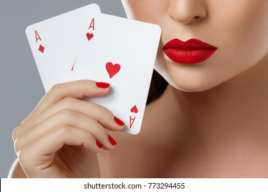 Poker or other card games. Woman with red lips is holding two aces in her hand