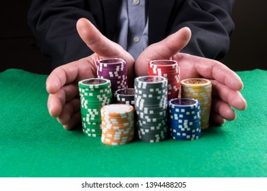 """Poker player going """"all in"""" pushing his chips forward on the table"""