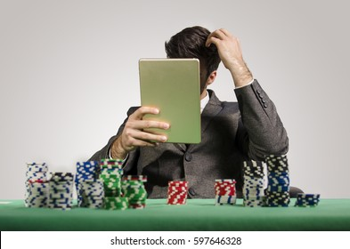 Poker player with hard decision, playing online, scratching his head