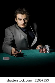Poker player holding chips, starring at his opponent
