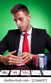 Poker player looking at his cards, on green background