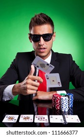 Poker player, on a green background, throwing two ace cards with full house on table