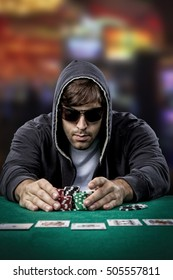 Poker player taking poker chips after winning, , on a casino background.