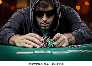 Poker player taking poker chips after winning, , on a bokeh lights background.