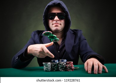 Poker player throwing poker chips on black background