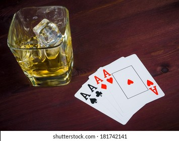 poker playing cards near wiskey glass on old wood table