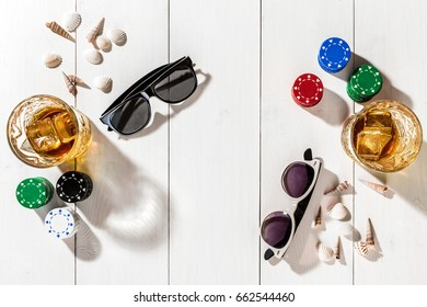 Poker. Set to playing poker with cards and chips on white wooden table, top view