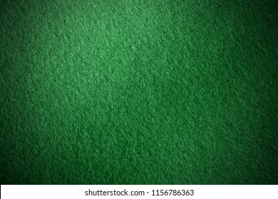 Poker table felt background in dark green color with shade vignette.