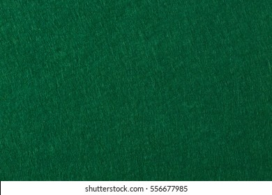 Poker table felt background in green color. High resolution photo.
