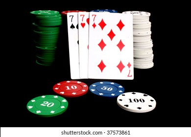 A poker winning hand called 'Three of a Kind' (consisting of three similar cards - sevens in this example) leaning on a stack of gambling chips, isolated on black studio background.