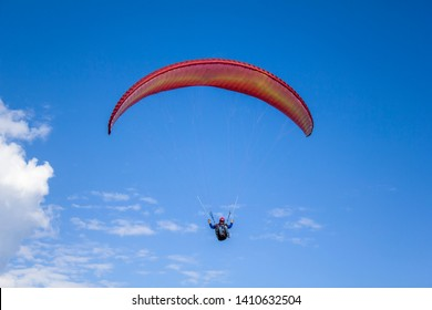 Pokhara, Nepal - 01.11.2018 paraglider with a helmet on a red parachute flying in a clear blue sky with white clouds, aerial view