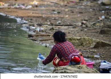POKHARA, NEPAL - APRIL 14,2019: Nepali local woman washing cloth along the Pokhara Lake with lake landscape, Pokhara